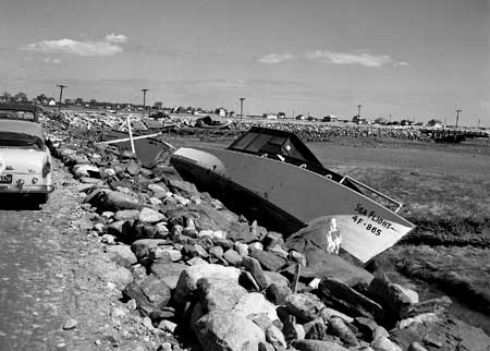 Wrecked boats line the rocks in the aftermath of hurricane Carol. Photograph by (Douglas Armsden, Portsmouth Athenaeum)