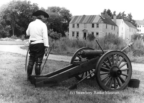 Revolutionary War re-enactor preps cannon at Strawbery Banke Museum in the mid-1860s. The as-yet-unrestored Joshua Jones house is in the background (c) Strawbery Banke Museum collection