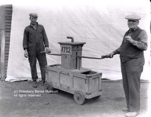 Former Portsmouth, NH bordello owner (right) and assistant display a 1792 fire pumper at Water Street antiques shop (c) Strawbery Banke Museum Collection / All rights Reserved