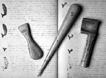 Working scrimshaw: shipboard tools made from sperm whale jawbone. Left to right: a sail creaser, a marlin spike about one foot in length, and a serving mallet used to wind spun yard around a rope. In the background is Leander S. Huntress' journal, kept onboard the Portsmouth whale ship Ann Parry and now in the Portsmouth Athenaeum. (Item in private collection, photo courtesy of Portsmouth Marine Society) SeacoastNH.com